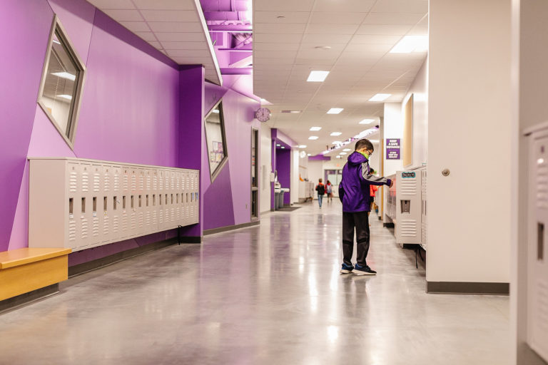 Corridor painted purple with lockers and child