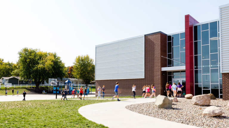 Exterior with playground and students entering building