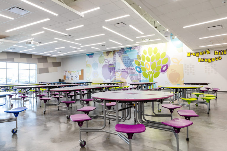 Lunchroom with tables and a mural