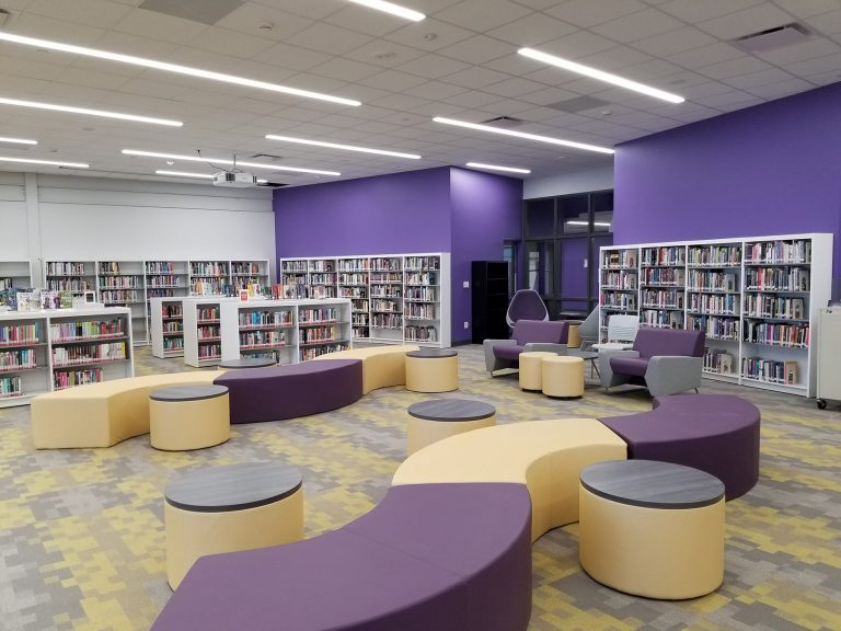 Media center with soft seating and purple accent wall