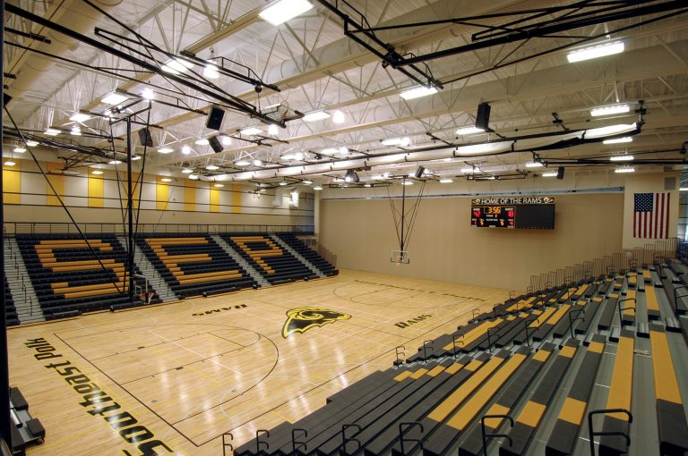 Gymnasium with exposed structure and lettering on bleachers