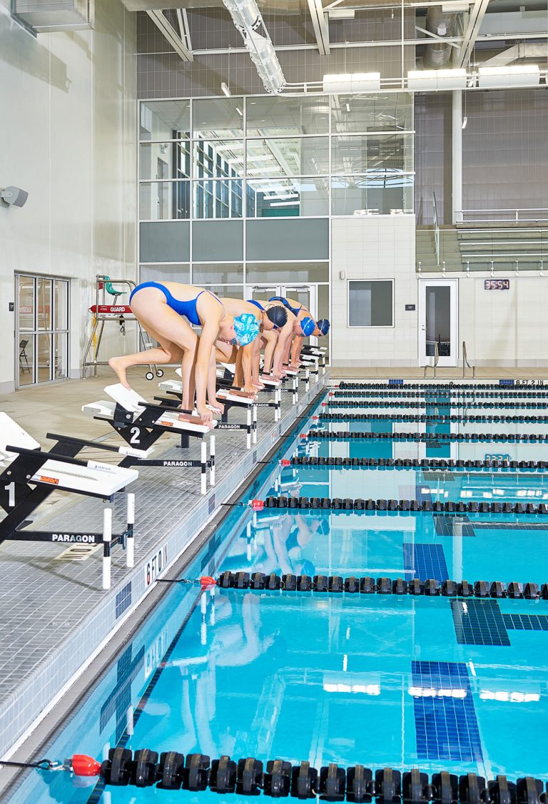 Swimmers preparing to dive in pool