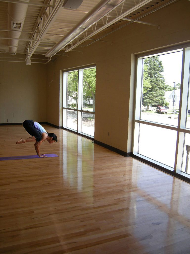 Woman practicing yoga on a purple mat in front of windows
