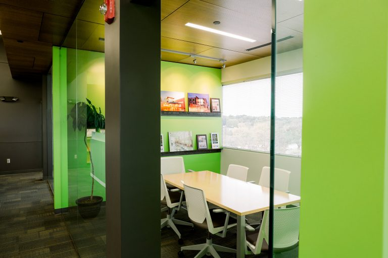 Conference room with green accent walls and awards